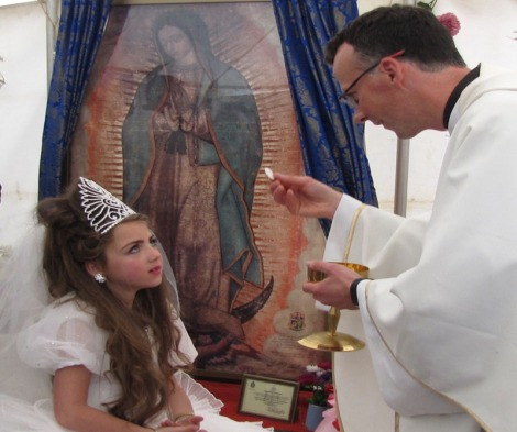 Young girl receives First Holy Communion near the Miraculous Relic Image