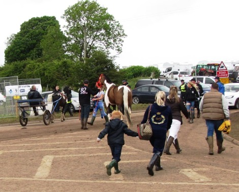 Busy crossroads with pony and trap, pedestrians, cars and caravans