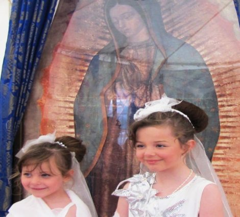Two little girls dressed in white before the Miraculous Relic Image