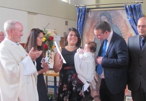 A baptism takes place before Our Lady of Guadalupe
